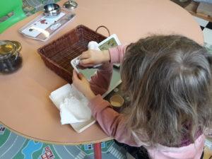 Fillette nettoyant un miroir, activité de vie pratique